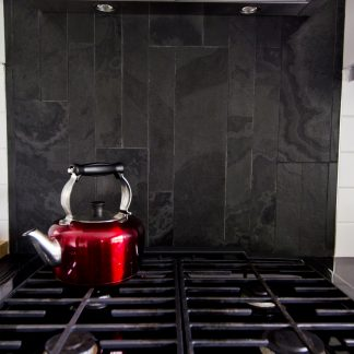 red kettle in front of grey slate back splash